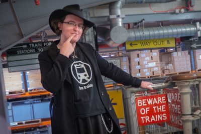 """Gemma posing next to a railway sign stating """"Beware of the Trains"""". Her t-shirt says """"I'm Trains"""" in internet slang."""
