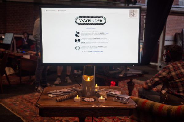 The game as displayed on a monitor, surrounded by LED candles atop a decorative, wooden table.